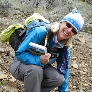 Jane Meissner smiles for a photo with plant guide in hand. Photo: Carolyn Waissman.