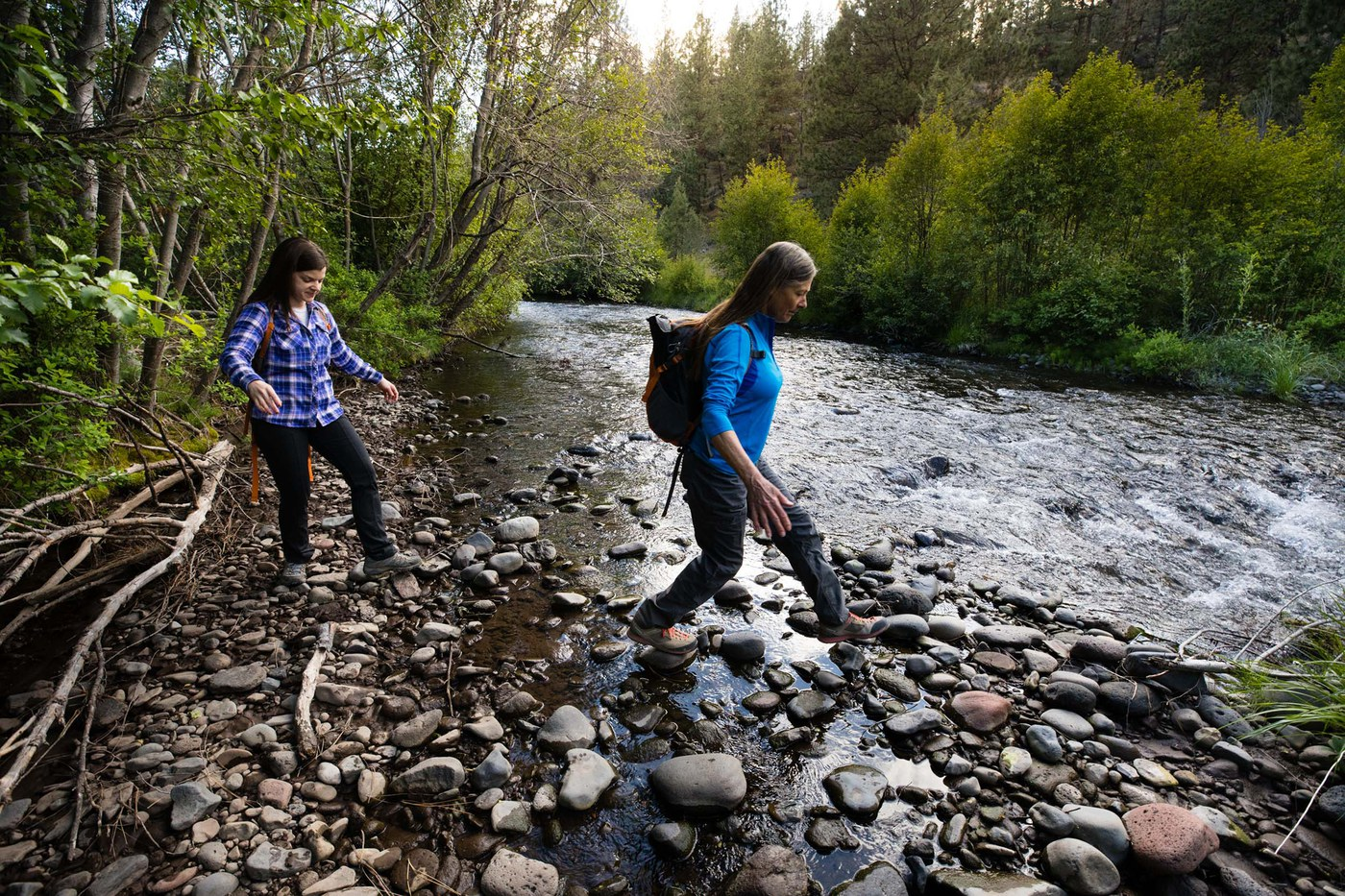 Women hike across stones at Whychus Creek. Photo: Tyler Roemer