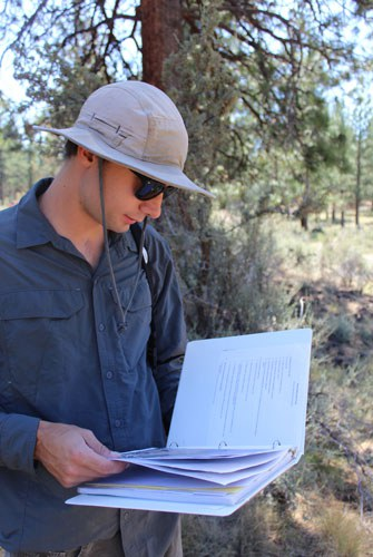 Taking a look at the monitoring notebook while out in the field. Photo: Land Trust.