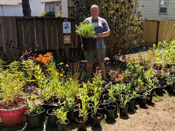Dennis and his tiny monarch waystation filled with milkweed. Photo: Robert Coffan.