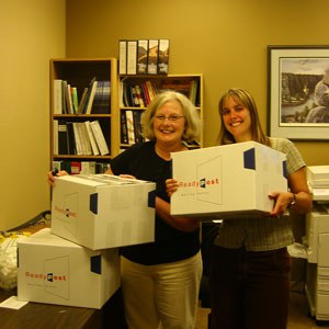 Pat Cohen and Lisa Bagwell with the boxes of materials required for national accreditation in2009. Photo: Land Trust.