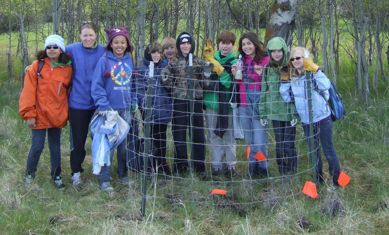 Students from Cascades Academy smile for a photo while working to cage aspen. Photo: Land Trust.